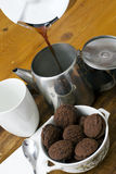 Fresh perculated coffee poured into a coffee pot. Fresh coffee poured into a coffee pot with white mug and chocolate biscuits Royalty Free Stock Photo