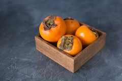 Fresh persimmon fruit on a table. Copy space. Close up. Stock Image