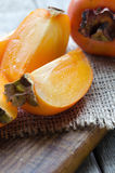 Fresh persimmon fruit on wooden board. Delicious fresh persimmon fruit on wooden cutting board Stock Photography