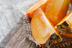 Fresh persimmon fruit on wooden board. Delicious fresh persimmon fruit on wooden cutting board Stock Image