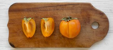 Fresh persimmon on a rustic wooden board over white wooden surface, top view. Flat lay, overhead, from above.  stock images