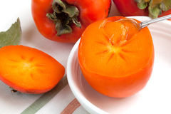 Fresh persimmon with a spoon Royalty Free Stock Photo