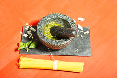 Fresh pesto Genovese in mortar and spaghetti on red Royalty Free Stock Photo