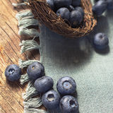 Fresh picked organic blueberries. Berries of blueberries scattered on a napkin from a wicker basket. Wooden table Stock Images