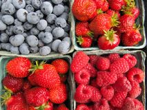 Fresh picked strawberries, raspberries and Blueberries. From home garden. Fruit in paper containers, square format Stock Image