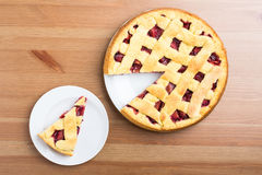 Fresh pie on a plate and table Royalty Free Stock Photos