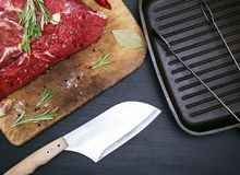 A fresh piece of beef on a kitchen cutting board. And a black frying pan Royalty Free Stock Images