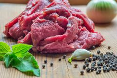 Fresh piece of beef meat in preparation on wooden desk. Piece of beef meat in preparation on wooden desk with black pepper, onion, garlic and mint leaves Stock Image