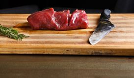 Fresh piece of filet mignon on wooden cutting board. Filet mignon. Slices of fresh beef meat, rosemary and sharp knife on wooden cutting board at modern royalty free stock image