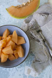 Fresh pieces of melon on bowl and slices on vintage scraped blue background Royalty Free Stock Photo