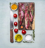 Fresh pieces of raw lamb on a chopping board, with herbs, spices, cherry tomatoes, lined rectangle on wooden rustic background top Stock Photography