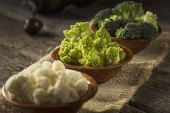 Fresh Raw Vegetables. Fresh pieces of Romanesco broccoli, broccoli and cauliflower in small rustic wooden bowls. Selective focus on the Romanesco broccoli Royalty Free Stock Images