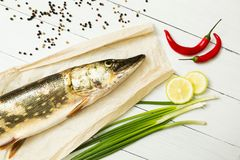 A fresh pike with spices on a white wooden background. European cuisine, river fish.  stock images