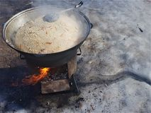 Fresh pilaf in a large cauldron cauldron is cooked on fire, outdoors in winter royalty free stock image