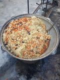 Fresh pilaf in a large cauldron cauldron is cooked on fire, outdoors in winter stock photography