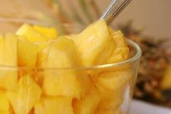 Fresh Pineapple Chunks. Fresh golden pineapple chunks in glass bowl with spoon Stock Photo