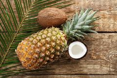 Fresh pineapple and coconuts on  background. Fresh pineapple and coconuts on wooden background Royalty Free Stock Images