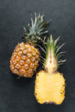 Fresh pineapple cut in half. Lay flat from above on dark slate Stock Image