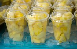 Fresh pineapple pieces salad in plastic transparent cups. For sale at farmers market royalty free stock photography