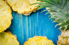 Fresh pineapple with slices on the wood texture background. Top Stock Photos