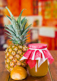 Fresh pineapple on a wooden table with a little bread and a glass pot, homemade.  Royalty Free Stock Photo