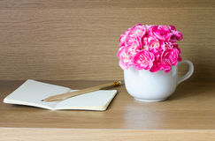 Fresh pink carnation flower with note book and pencil on wooden Stock Photos