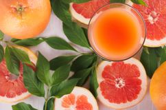 Fresh pink juice and grapefruits with green leaves top view as tropical summer background. stock photo