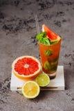 Fresh pink lemonade with lemon, lime and strawberries. Black background stock image