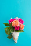 Fresh pink and orange roses in paper cover over blue background Royalty Free Stock Image