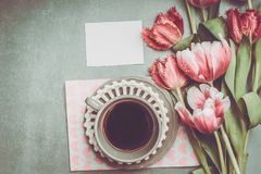 Fresh pink pale tulips bunch with heart, blank paper and cup of coffee , top view. stock photos
