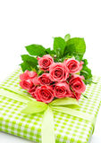 Fresh pink roses with gift isolated on white Stock Photo