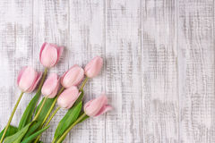 Fresh pink tulip flowers bouquet on white wooden rustic table Stock Photo
