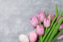 Fresh pink tulip flowers and easter eggs. On stone table. Top view with copy space Royalty Free Stock Photo