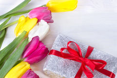 Fresh pink tulip flowers in gift box on wooden table. Royalty Free Stock Image