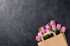 Fresh pink tulip flowers. In paper bag on dark stone table. Top view with copy space Stock Photo