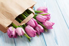 Fresh pink tulip flowers in paper bag. On wooden table Stock Images