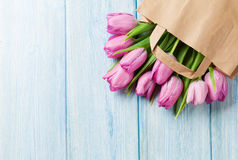 Fresh pink tulip flowers. In paper bag on wooden table. Top view with copy space Royalty Free Stock Photography