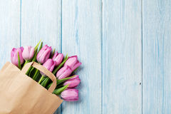 Fresh pink tulip flowers in paper bag. On wooden table. Top view with copy space Stock Photos