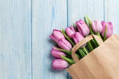 Fresh pink tulip flowers in paper bag. On wooden table. Top view with copy space Royalty Free Stock Photography