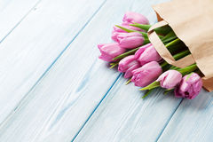 Fresh pink tulip flowers in paper bag. On wooden table. Top view with copy space Stock Photography