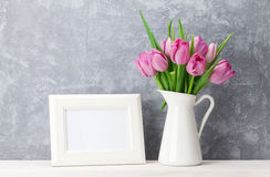 Fresh pink tulips bouquet and photo frame. Fresh pink tulip flowers bouquet and blank photo frame with copy space on shelf in front of stone wall Stock Photography