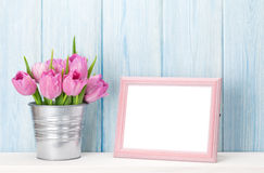 Fresh pink tulips bouquet and photo frame. Fresh pink tulip flowers bouquet and blank photo frame with copy space on shelf in front of wooden wall Stock Photography