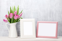 Fresh pink tulips bouquet and photo frames Royalty Free Stock Photography