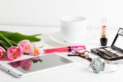 Fresh pink tulips, white tablet, cosmetics, wristwatch. Cup of coffee, glasses - spring female things stock image