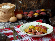 Fresh pink yellow beet dumplings or ravioli stuffed with ricotta cheese with butter sauce on wooden board on dark background. Stock Photos