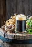 Fresh pint of dark beer, hops and wheat on old barrel Stock Photos