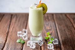 Fresh pistachio cocktail with kiwi. On a wooden background Royalty Free Stock Image