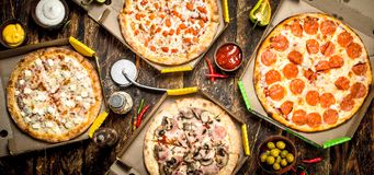Fresh pizza in boxes. On a wooden background royalty free stock photos