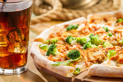 Fresh pizza with broccoli and chicken served with cold cola Stock Photos
