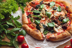 Fresh pizza with ingredients on wooden table Royalty Free Stock Photos